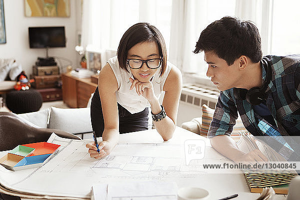 Young woman analyzing blueprint with man at home