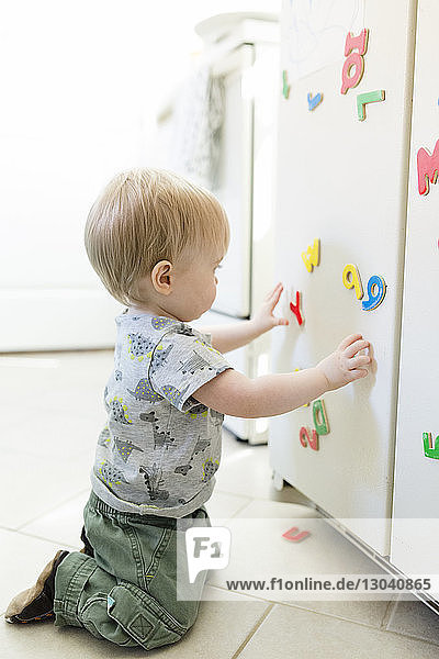 Side view of baby boy playing with colorful magnetic letters and numbers on metallic cabinet at home