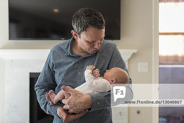 Vater trägt neugeborenen Jungen zu Hause