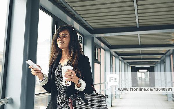 Happy woman looking away while standing on footbridge