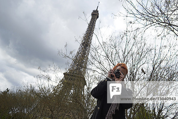 Low angle view of photographer using digital camera against Eiffel Tower