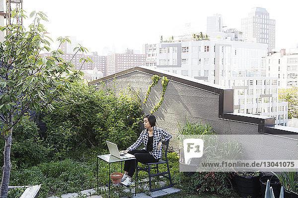 Frau benutzt Laptop auf der Terrasse