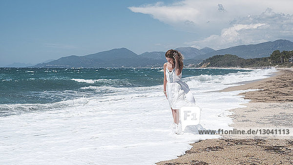 Woman walking in waves at beach against cloudy sky