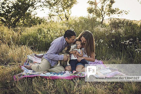 Glückliche Familie sitzt auf Picknickdecke mit Hund auf dem Feld