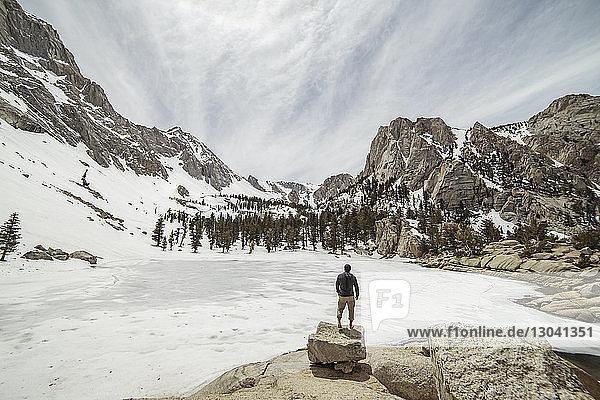 Rückansicht eines Wanderers  der auf Felsen stehend die Aussicht betrachtet