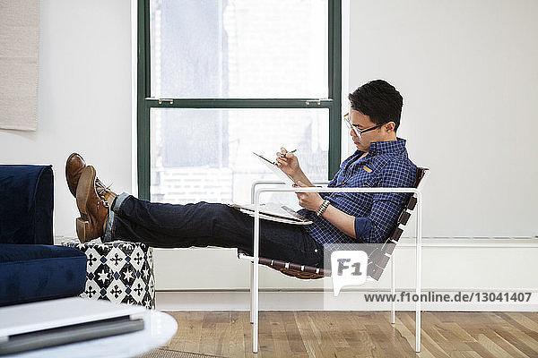 Seitenansicht eines Geschäftsmannes beim Lesen der Zwischenablage im Kreativbüro Seitenansicht eines Geschäftsmannes beim Lesen der Zwischenablage im Kreativbüro
