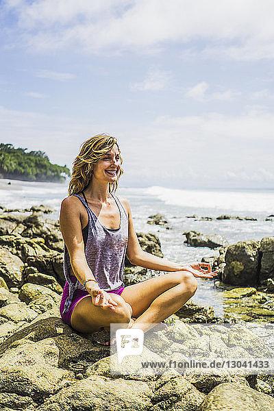 Glückliche Frau im mittleren Erwachsenenalter sitzt im Lotussitz auf Felsen am Strand