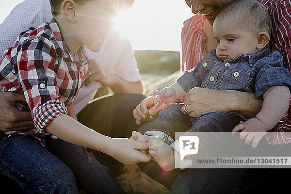 Junge berührt die Füße des Bruders  während er am sonnigen Tag bei den Eltern am Strand sitzt
