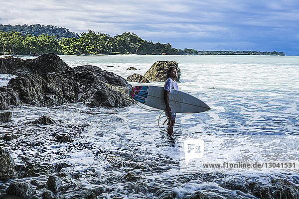 Seitenansicht eines am Strand stehenden Surfers mit Surfbrett