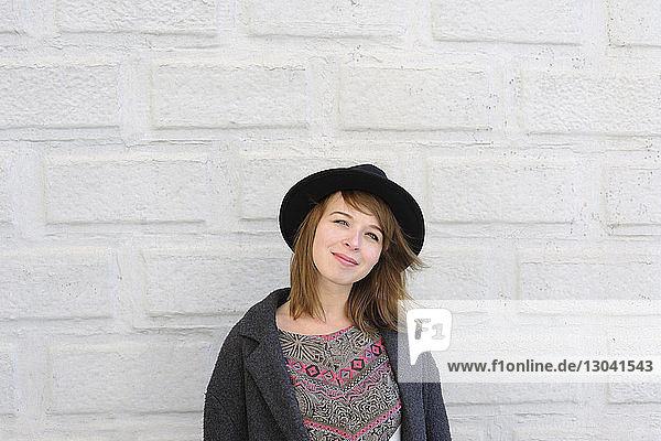 Porträt einer lächelnden Frau mit Hut  die an der Wand steht