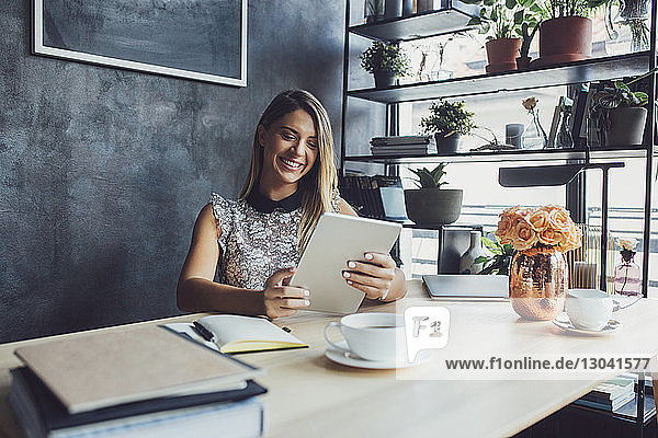 Happy businesswoman using tablet computer while sitting at table in home office