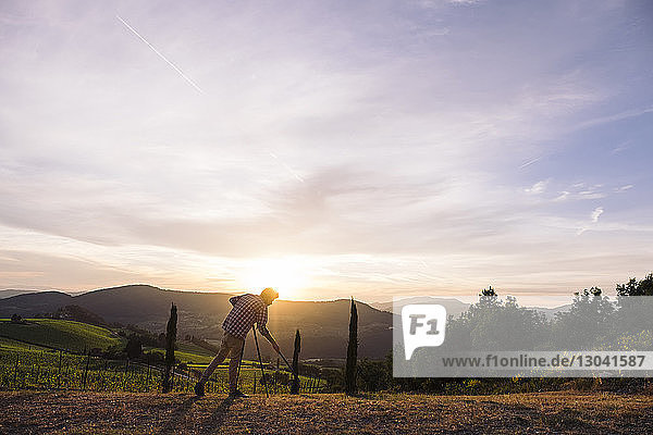 Full length of photographer adjusting tripod on field against sky during sunset