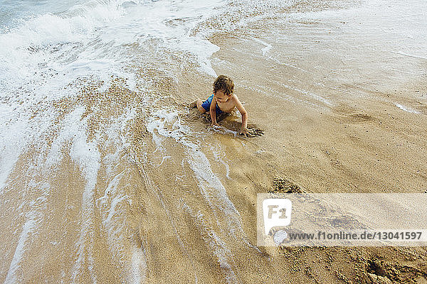 High angle view of shirtless boy playing on shore at beach