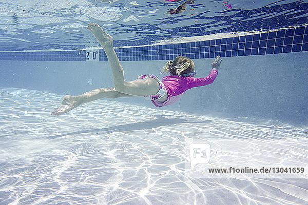 Mädchen schwimmt in voller Länge unter Wasser im Pool
