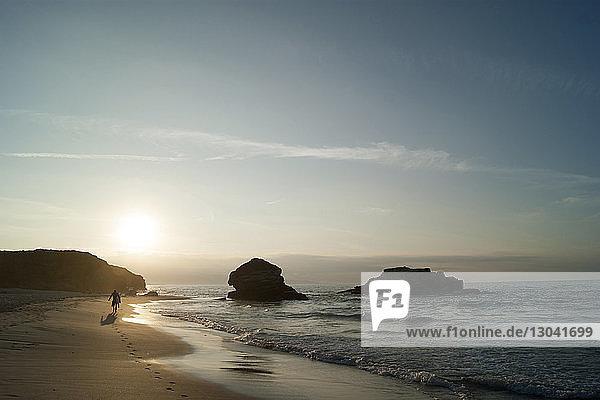Silhouettenmann in voller Länge mit Surfbrett  der bei Sonnenuntergang am Strand gegen den Himmel läuft