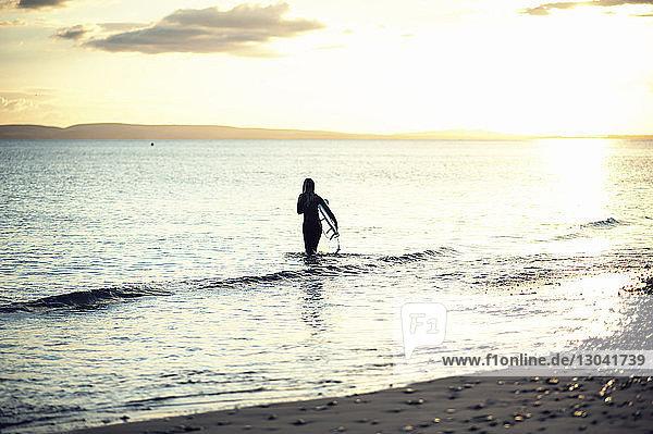 Rückansicht einer Frau  die ein Surfbrett trägt  während sie bei Sonnenuntergang im Meer gegen den Himmel läuft