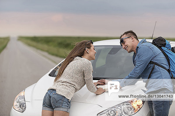 Happy couple looking at each other while leaning on car hood with diary against sky