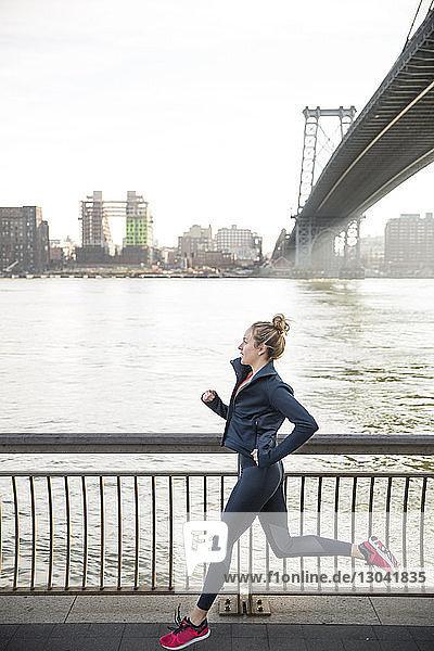 Seitenansicht eines Athleten  der auf der Promenade am East River läuft