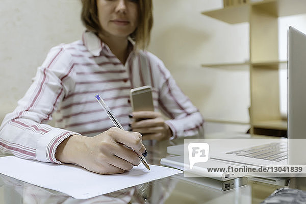 Midsection of businesswoman writing on paper while working at home office
