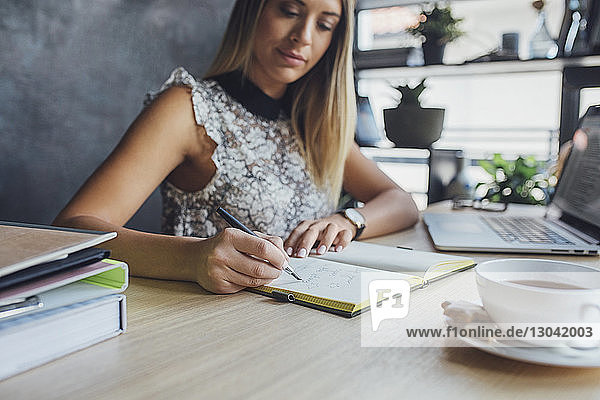 Businesswoman writing on diary while sitting at table in home office
