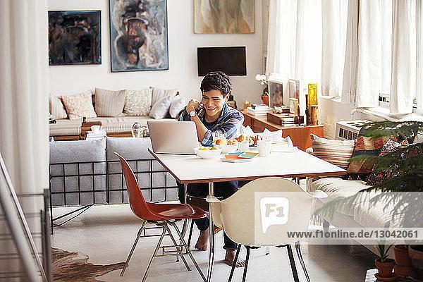 Glücklicher Mann benutzt Laptop zu Hause