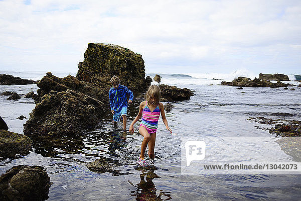 Brother and sister walking in water by rocks at Laguna Beach
