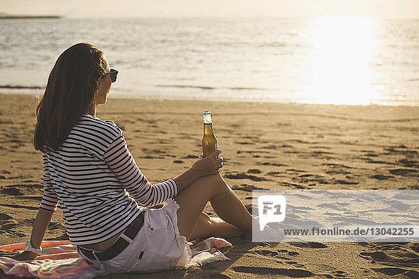 Seitenansicht einer Frau  die bei Sonnenuntergang am Strand eine Bierflasche in der Hand hält