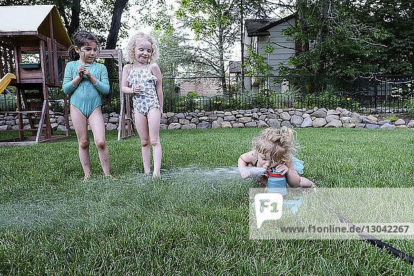 Freunde schauen einem Mädchen zu  das Wasser aus einem Sprinkler auf einem Spielplatz trinkt
