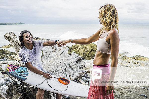 Glücklicher männlicher Surfer hält Frauenhand  während er auf Treibholz am Strand sitzt