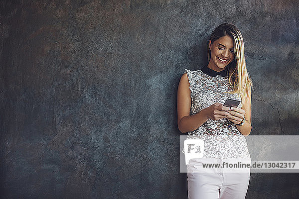 Happy businesswoman using smart phone while standing against wall at home office