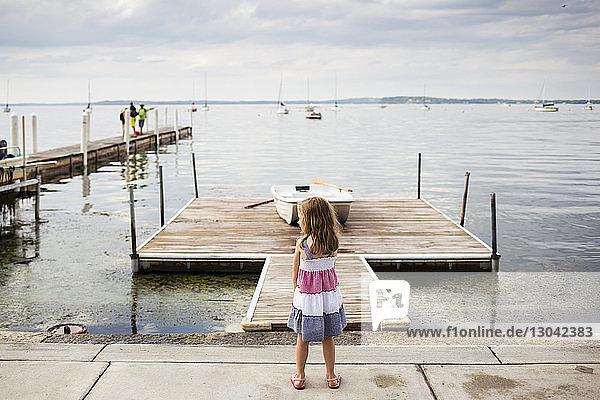 Rückansicht eines Mädchens  das weg schaut  während es am Meer vor bewölktem Himmel steht