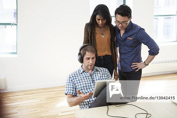 Geschäftsleute  die einen Tablet-Computer im Kreativbüro benutzen