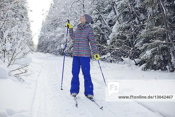 Frau in Skikleidung in voller Länge  die aufschaut  während sie auf einem schneebedeckten Feld steht