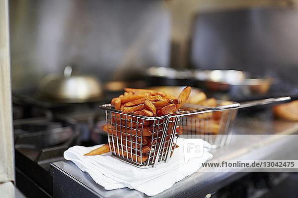 Nahaufnahme von Pommes Frites im Frittierkorb auf der Küchentheke
