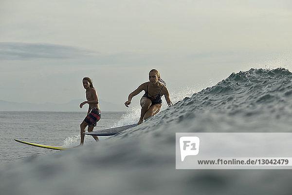 Freunde  die im Meer gegen den Himmel surfen