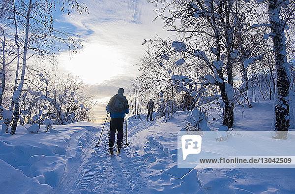 Rückansicht von Skifahrern auf schneebedecktem Feld gegen den Himmel