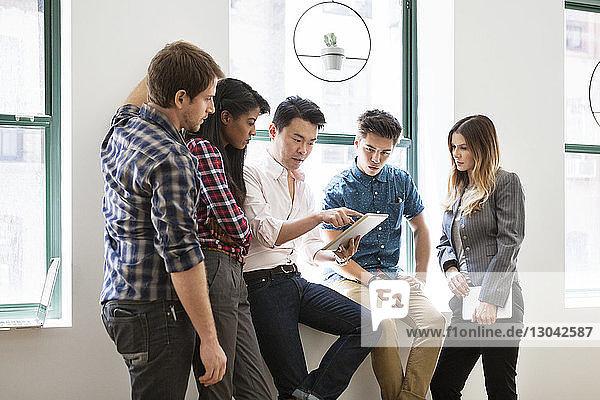 Geschäftskollegen mit Tablet-Computer am Fenster im Kreativbüro
