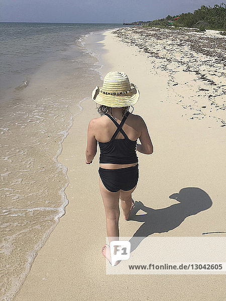 Rear view of girl wearing sun hat walking at beach during sunny day