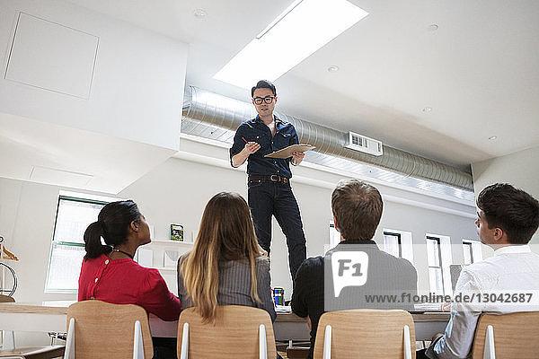 Geschäftsmann diskutiert mit Kollegen  während er im Kreativbüro am Schreibtisch steht