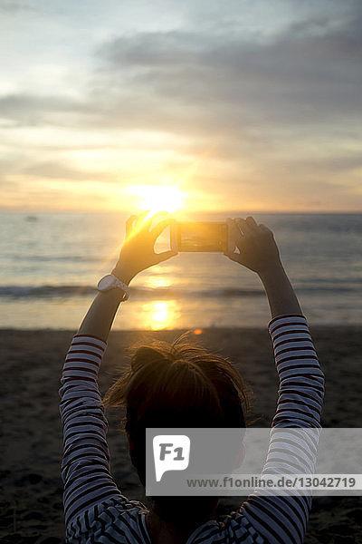 Rückansicht einer Frau  die bei Sonnenuntergang am Strand fotografiert