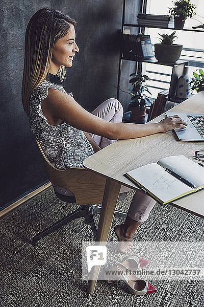 Side view of businesswoman using laptop computer while sitting at table in home office
