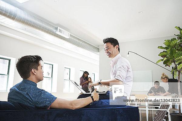 Glücklicher Geschäftsmann diskutiert mit Kollege im Kreativbüro