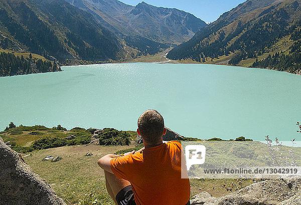 Rear view of man looking at view while sitting at lakeshore