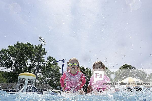 Glückliche Schwestern sitzen am Schwimmbad gegen den Himmel