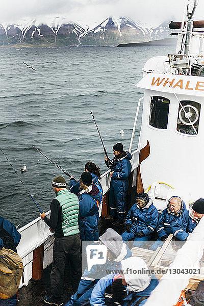 Hochwinkelaufnahme von Menschen  die während der Fahrt im Boot auf See fischen