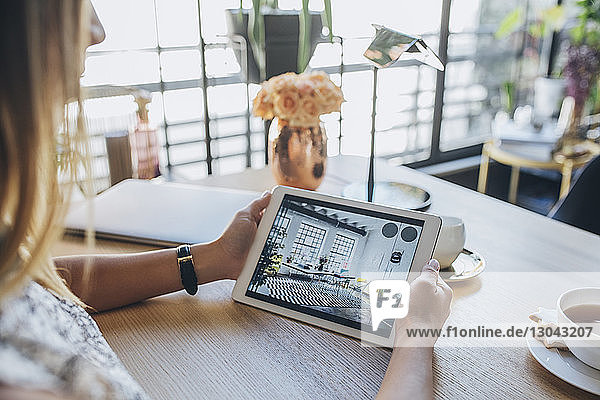 Cropped image of businesswoman holding tablet computer while sitting at table