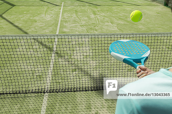 Midsection of woman hitting tennis ball with racket on court