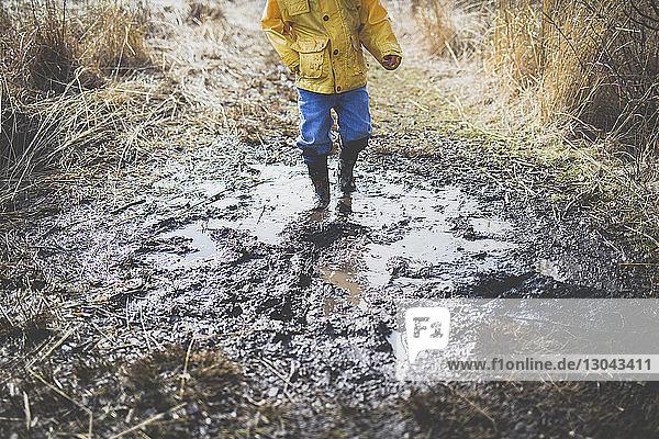 Niedriger Teil eines Jungen  der in einer schmutzigen Pfütze läuft