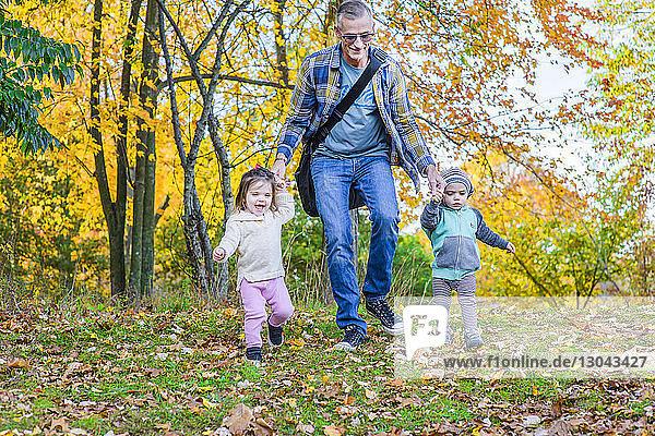 Glücklicher Vater mit Töchtern  die im Herbst auf einem Grasfeld im Wald spazieren gehen