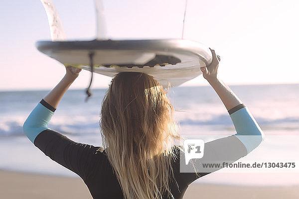 Rückansicht einer Frau  die am Strand stehend ein Surfbrett auf dem Kopf trägt